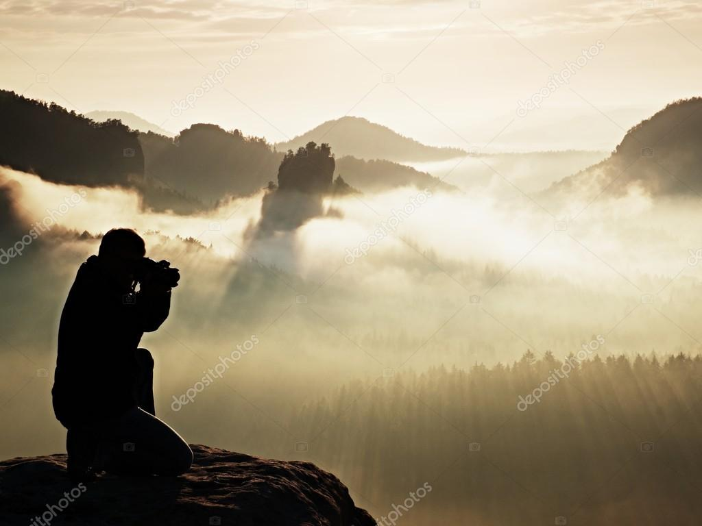 Professional photographer silhouette above a clouds sea, misty mountains