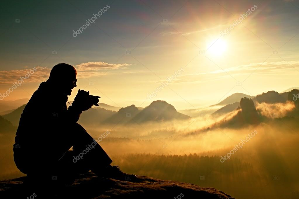 Photograph takes photos of daybreak above  heavy misty valley. Landscape view of misty autumn mountain hills and happy man silhouette