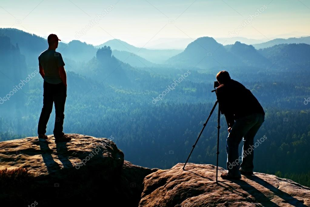 Tourist guide and photo enthusiast stay with tripod on cliff and thinking. Dreamy fogy landscape, blue misty sunrise in a beautiful valley below