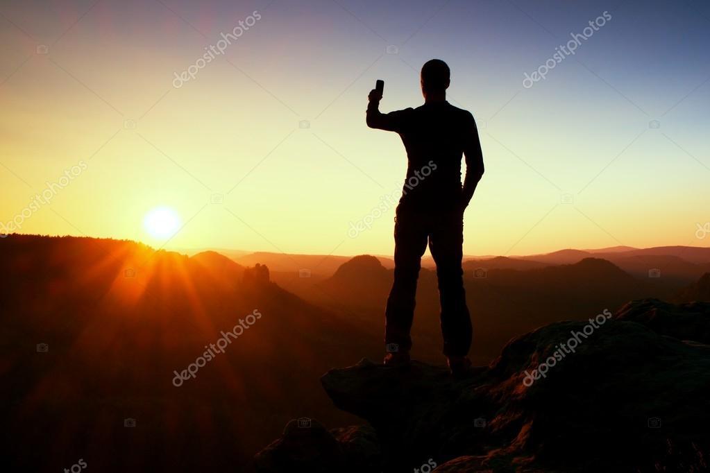 Selfie mania. Tall man hiker is taking selfie photo by smart phone on peak of mountain at sunrise.
