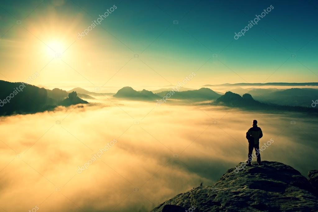 Man stands on peak of sandstone rock in Saxony Switzerland park and watching to Sun. Beautiful miracle of nature