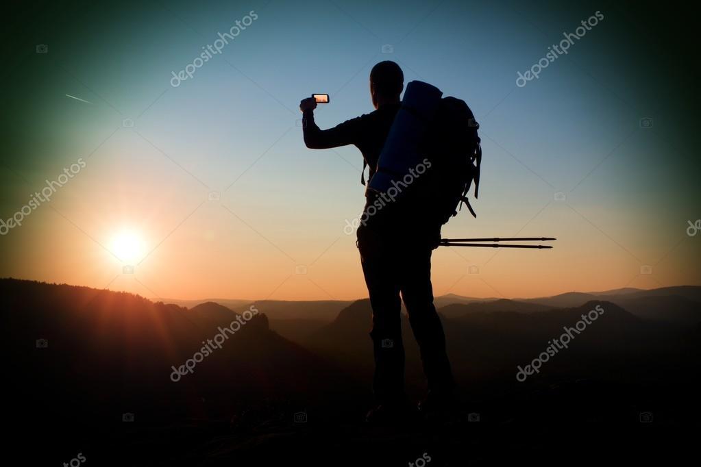 Strong man hiker taking photo with smart phone at mountain peak. Daybreak at horizon