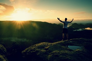 Runner on the peak. Man in his target gesture triumph with hands in the air. Crazy man in black pants and white cotton t-shirt,