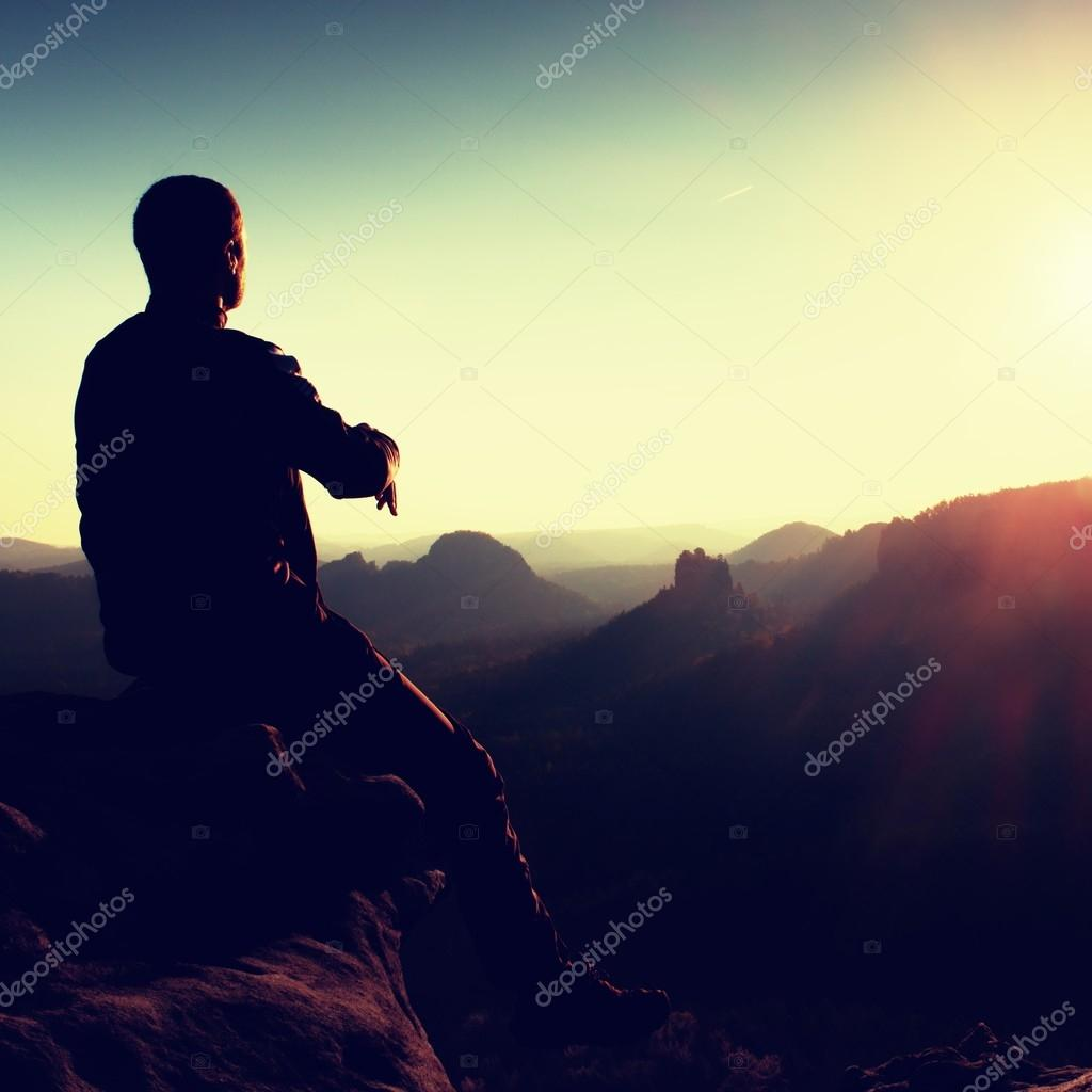 Tired hiker take a rest in nature.  Mountain summit above forest in valley. Traveling in European  natural parks.