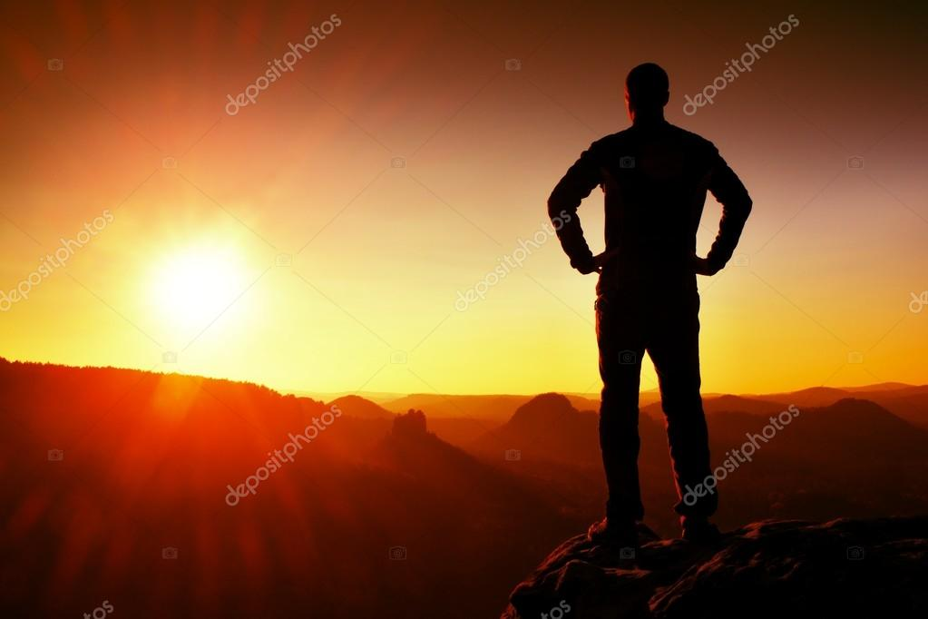 Silhouette of Young Confident and Powerful Man Standing with Hands on Hips, Morning Or Late Day Sun with Copy Space