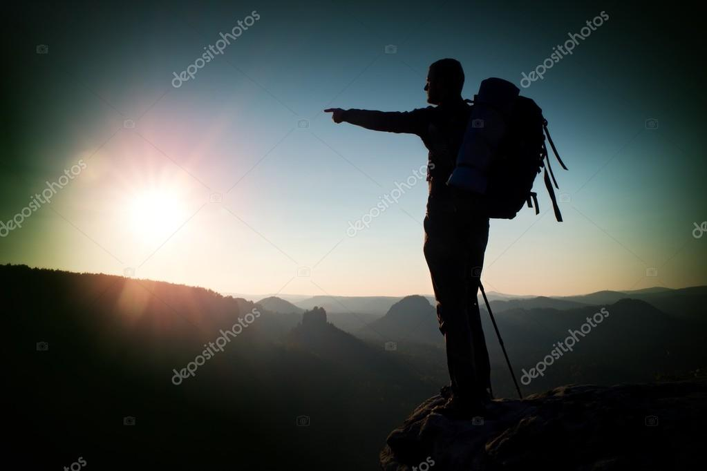 Tourist on peak. Sunrise with inversion.Cliff above deep autumn valley with tourist guide on top. Hiker watch breathtaking  beautiful scenery