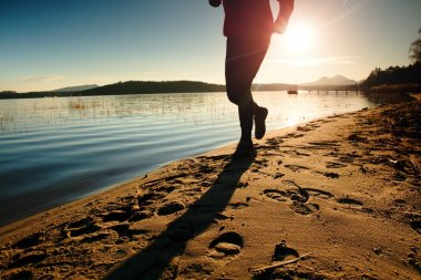 Tall man in sportswear at amazing sunset in sport and healthy lifestyle concept and jogging cross country training workout