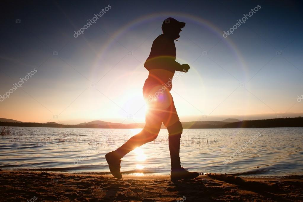 Runner in Sun rays on beach. Sportsman in baseball cap, jogging during the sunrise above sea