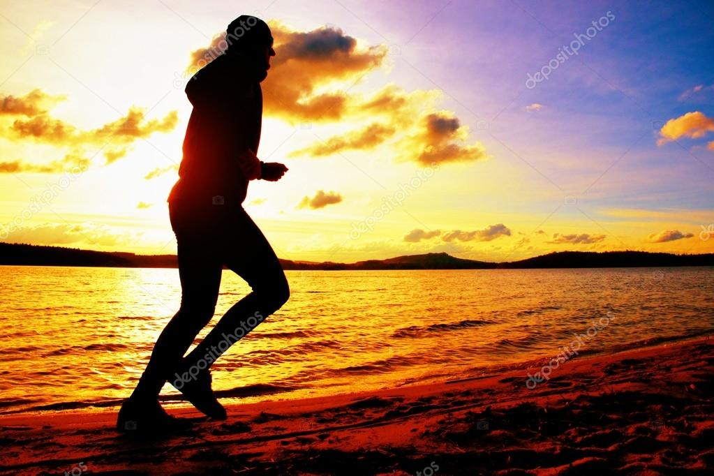 Silhouette of sport active man running and exercising on beach at vivid colorful sunset.