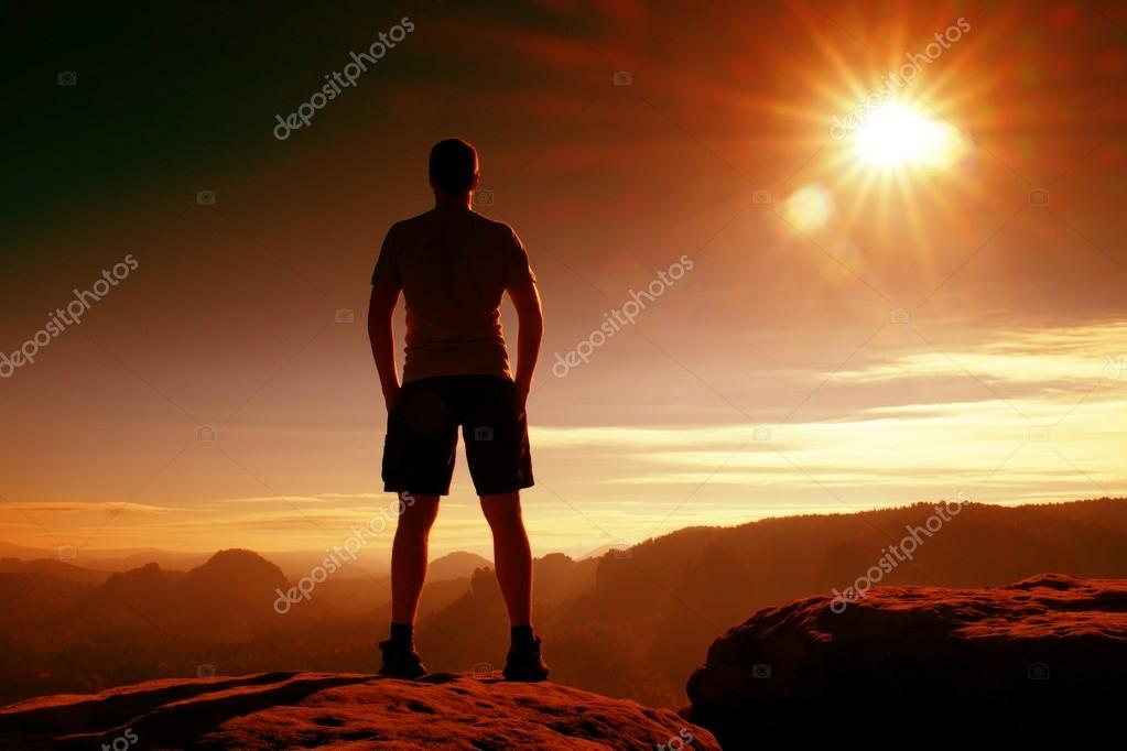 Red filter photo. Slim tourist in pants on the cliff of rock empire is watching down to valley. Hot Sun above.