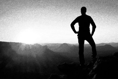 Black and white dashed retro sketch. A man has his hands on  hips. Sportsman  silhouette in nature.