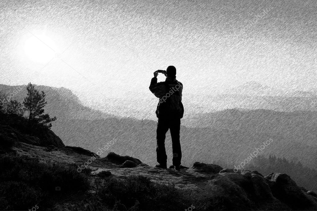 Black and white dashed retro sketch. Hiker is taking photo by smart phone on the peak of rock