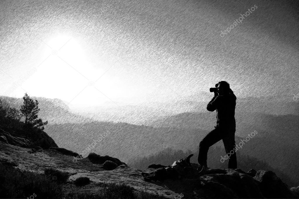 Black and white dashed retro sketch. Professional photographer takes photos with mirror camera on peak of rock.