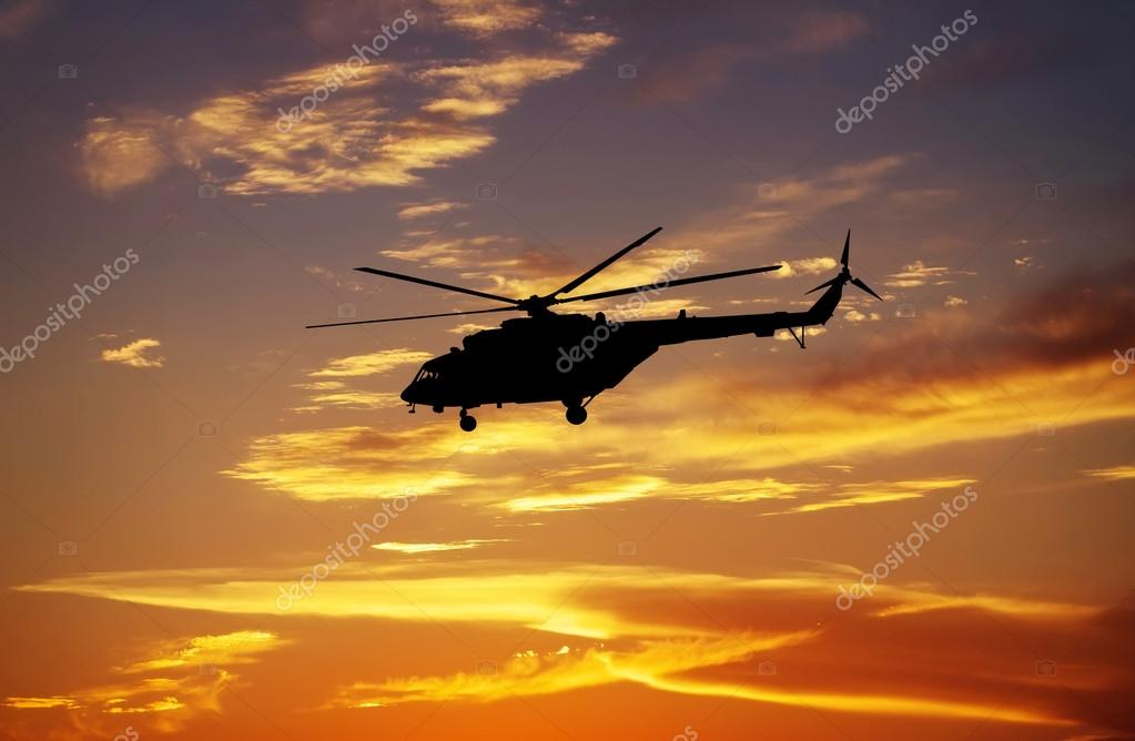 Picture of helicopter at sunset. Silhouette of helicopter on sun