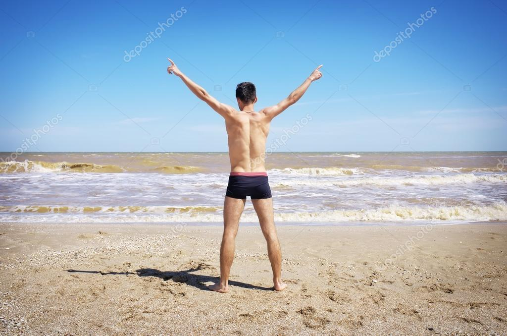 Back view of Young man spread his hands on beach.