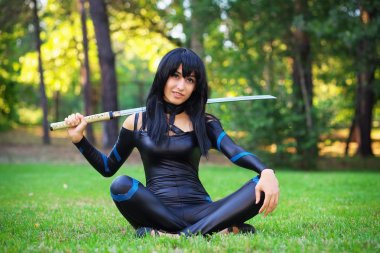 Young girl sitting on the grass and holding samurai sword.