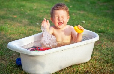 A small happy baby bathed in the bath and playing in a bath