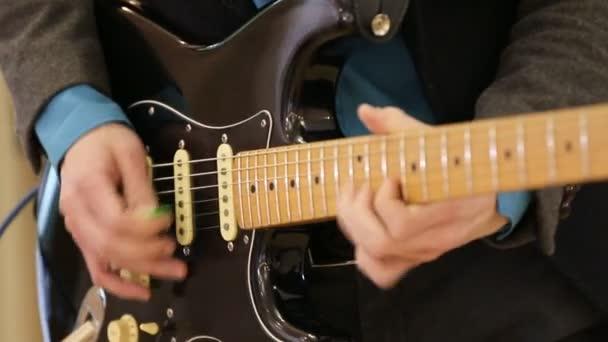 Detailní záběr mužských rukou hrajících na akustickou kytaru. Kytarista hraje na pódium klasickou kytaru na koncertě. Kytara. hudební skupina