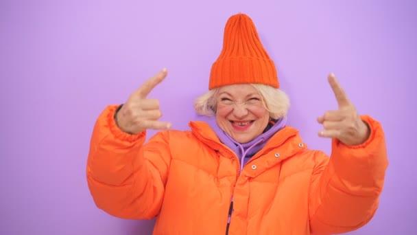 Aktive Ältere Frau zeigt Rock n Roll-Handbewegung, Spaß haben, isolierten Hintergrund im Studio