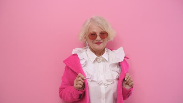selbstbewusste, glückliche ältere Dame in modischem Mantel und stylischer rosafarbener Brille posiert vor isoliertem Hintergrund für die Kamera