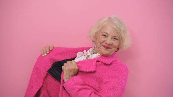 Eine optimistische Rentnerin denkt nicht an ihr Alter, ihr Alter. Eine Frau mit blonden Haaren im modischen rosa Mantel posiert für die Kamera, isolierter Hintergrund.