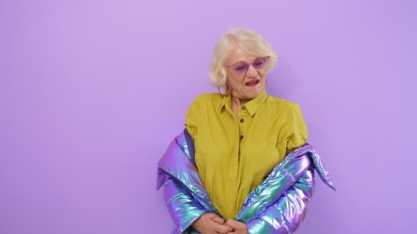 Glückliche ältere Frau mit Brille posiert im Studio und probiert helle moderne Kleidung an.