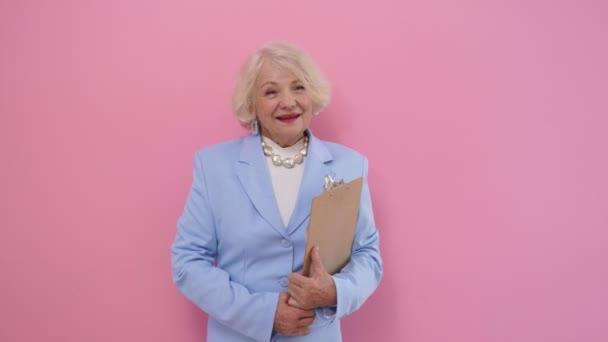Porträt einer eleganten älteren Frau im eleganten Business-Anzug, die ein Tablet in der Hand hält und in die Kamera lächelt