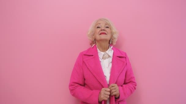 hübsche ältere Dame in einem eleganten rosa Mantel mit gesunder, frischer Haut posiert in einem Studio
