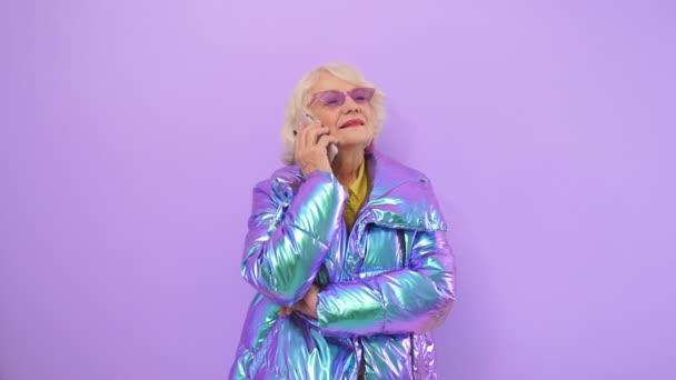 stylische Frau im Rentenalter in heller modischer Jacke und Brille, die auf einem isolierten Hintergrund im Studio telefoniert