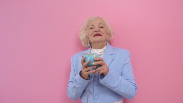 Frau mit blonden Haaren denkt nicht an ihr Alter, Alter im modischen Anzug, der vor der Kamera posiert, isolierter Hintergrund.