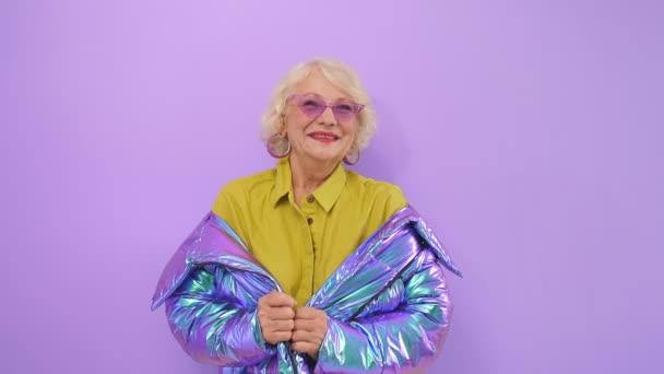 Nette, positive alte Dame lächelnd posiert im Studio vor isoliertem Hintergrund