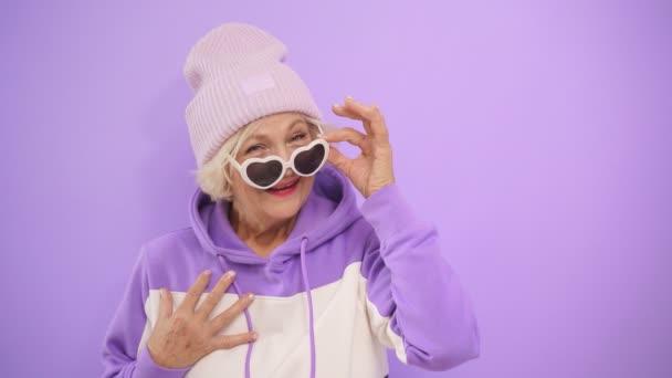 glücklich Reife Frau mit stylischer Brille und Hut Gesten stehen auf einem isolierten Hintergrund