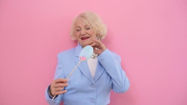 Erstaunlich, schöne Ältere Frau im modischen blauen Anzug posiert für die Kamera auf rosa Hintergrund im Studio