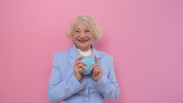 fröhliche Rentnerin, glücklich mit dem Leben, lächelt glücklich, posiert im Studio vor isoliertem Hintergrund für die Kamera