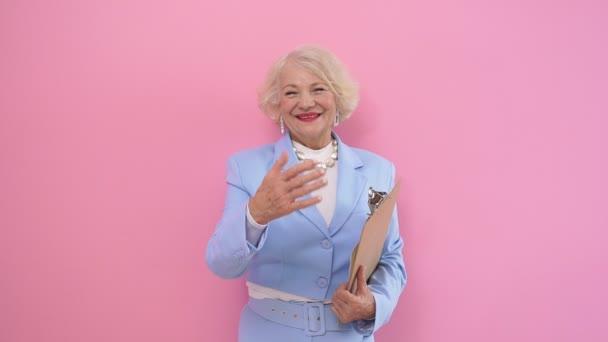 Lächelnde Ältere Dame im blauen Business-Anzug, die ein Tablet in der Hand hält, grüßt, zieht zum Händeschütteln