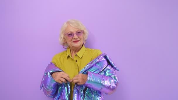 Moderne ältere Frau mit einem Lächeln genießt ihr Alter, wenn sie vor isoliertem Hintergrund für die Kamera posiert