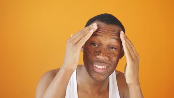 Porträt eines jungen Afroamerikaners mit einem Peeling im Gesicht, während er lächelt und für die Kamera posiert, isolierter Hintergrund