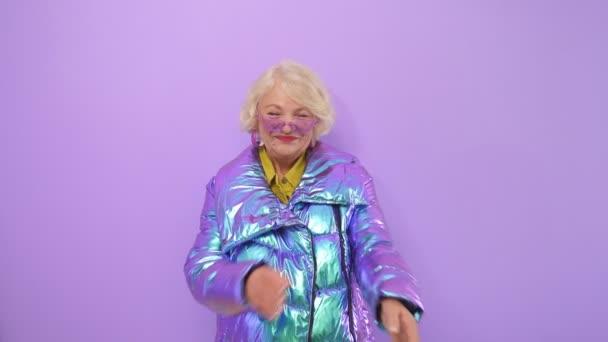 Attraktive ältere Frau mit Brille und blonden Haaren blickt lächelnd in die Kamera und posiert in heller Jacke vor isoliertem Hintergrund im Studio