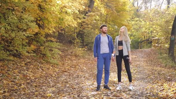 young athletic couple enjoys Hiking on the road through a beautiful autumn forest, exercise and fitness concept