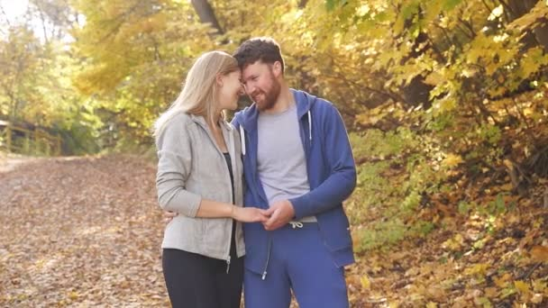 Caucasian couple happy together, young couple enjoying each other in the autumn forest on a Sunny day after a run in the fresh air