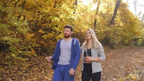 happy man and woman walking in the autumn forest after a run in the fresh air, a young couple loves to walk in the forest in the fall