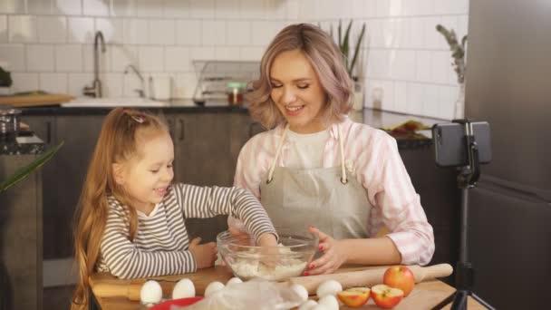šťastná žena, video blogger, video on-line školení vaření v kuchyni doma, holčička se svou matkou miluje vařit doma