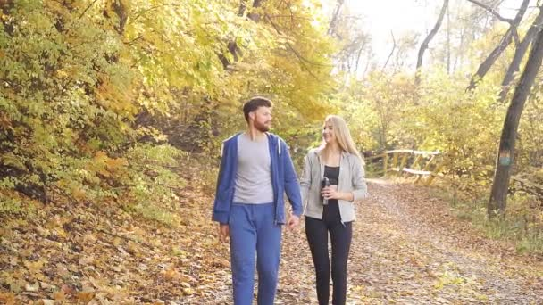 happy young couple in sports clothes after a run on a Sunny day strolling through the autumn forest among colorful yellow trees
