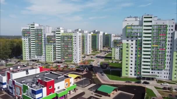 View of modern apartment buildings and a kindergarten with bright colorful facades from a birds eye view, a new residential neighborhood for urban residents, drone shooting