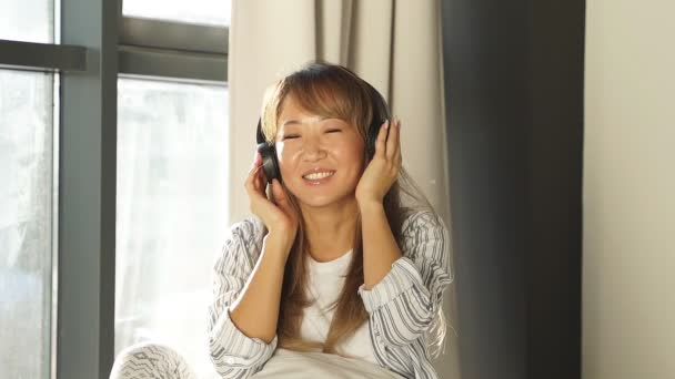 beautiful Japanese woman listening to music in bed, woman enjoying a day off
