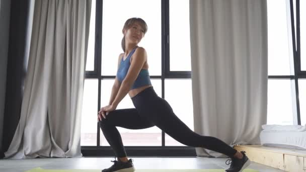 gyönyörű nő csinál gyakorlatokat egy fitness szőnyeg a nappaliban, gyakorlatok, hogy növelje a test rugalmasságát