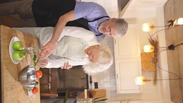 V kuchyni připraví krásný dospělý pár zeleninový salát s čerstvou zeleninou. Starší muž a žena jsou šťastní, že spolu vaří