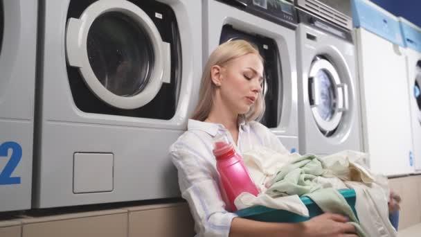 Eine Frau, die in einer öffentlichen Waschküche neben einer Waschmaschine sitzt, ist es leid, darauf zu warten, dass ihre Kleidung in einer Haushaltswaschmaschine gewaschen wird