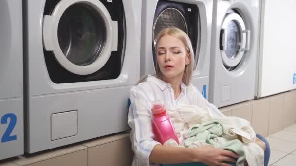 Egy nő ül a mosókonyha padlóján a mosógépek mellett, nagyon belefáradt abba, hogy várja a mosást. Egy fáradt nő várja a tiszta ruhákat a mosodában.