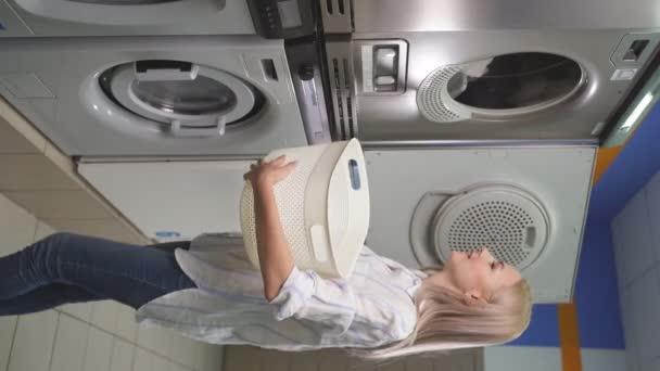 Függőleges felvétel egy fiatal nőről, amint mosogat egy mosógépben egy nyilvános mosókonyhában.